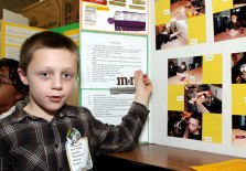 """Robert Hanson, 8, explains the results of his edible chocolate melting experiment. He predicted that M&Ms would melt the slowest because of their hard candy coating. His hypothesis proved correct, but he also found that chocolate with higher coco content took longer to melt. """"I love chocolate,"""" Hansen said when asked why he chose that experiment."""