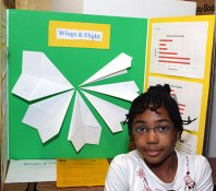 """Helen Meade, 8, made paper airplanes with varying wingspans to see which would fly the furthest. She thought the widest winged plane would fly the best, but the opposite proved true. """"I'm really good at making paper airplanes,"""" she said."""