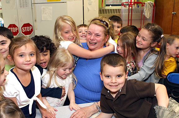 Students at Tender Years Preschool give Gigi Ramos a big hug. Ramos sponsored Sparkles the Clown who entertained the kids with her silly magic tricks May 13.