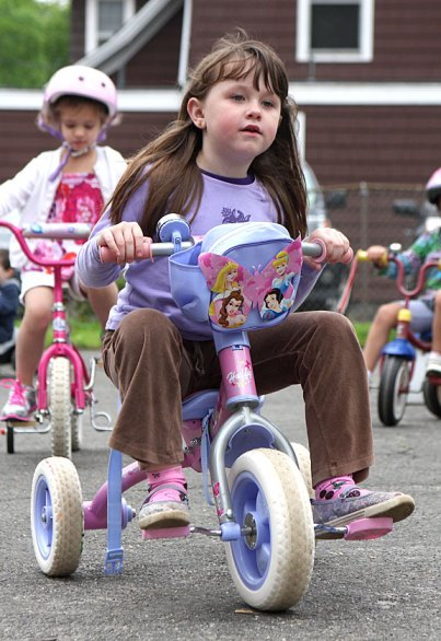 Maya Dias peddles around the parking lot of Tender Years Preschool in Naugatuck during the annual Trike-a-Thon May 20.