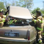 Firefighters from Beacon Hose Co. No. 1 lift off a car roof after it was cut apart to help free victims during the mock crash.