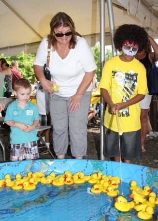 From left, Kai Cioana, 2, Sandy Sobota, and Darrick Waller, 9, fish for ducks at Naugatuck Duck Day June 5.