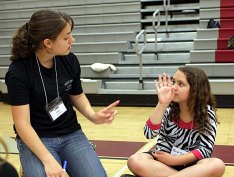 Naugatuck High School student Megan Wilson, left, discusses leadership qualities with her younger peer, Keziah Cabral, right.