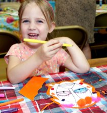 Clair Cummings, 4, decorates a mask July 14 as part of a children's program at the Beacon Falls Library.