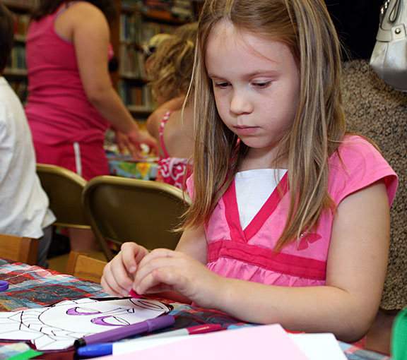 Cayleigh Cummings, 7, decorates a mask July 14 as part of a children's program at the Beacon Falls Library.