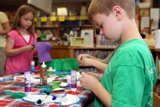 Noel Cummings, 9, decorates a mask July 14 as part of a children's program at the Beacon Falls Library.