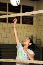 Maria Contraras, 13, taps the ball over the net during volleyball camp July 14.
