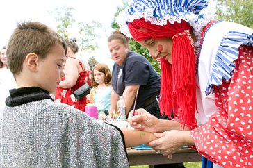 Mary 'Lollipop' Toma, with Party Troupe, paints a snake on Carter Evon, 5, during End of Summer Fun Week on the Prospect Town Green Aug. 22. Monday was character day and featured face painting, train rides, and ice cream.