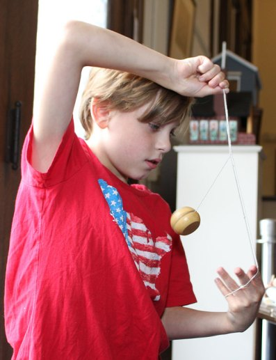 """Johnathan McPhail, 9, plays with a yo-yo during a children's program, """"Yesterday's Toys and Games,"""" at the Naugatuck Historical Society Aug. 5."""