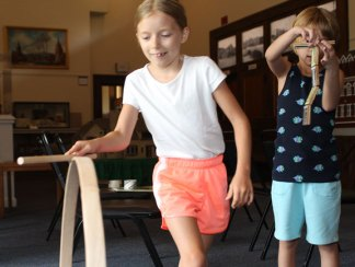 """Sarah Hofmann, 8, plays with an old-fashioned stick and hoop during a children's program, """"Yesterday's Toys and Games,"""" at the Naugatuck Historical Society Aug. 5."""