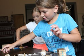 """Sarah Hofmann, 8, left, and Juliana Sarbieski, 7, play with spinning tops during a children's program, """"Yesterday's Toys and Games,"""" at the Naugatuck Historical Society Aug. 5."""