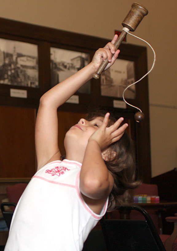"""Shaylin Fisher, 7, plays with a cup and ball toy during a children's program, """"Yesterday's Toys and Games,"""" at the Naugatuck Historical Society Aug. 5."""