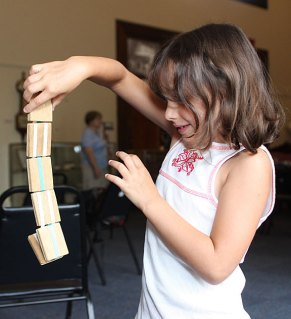 Shaylin Fisher, 7, plays with a jabob's ladder toy during a children's program at the Naugatuck Historical Society Aug. 5.