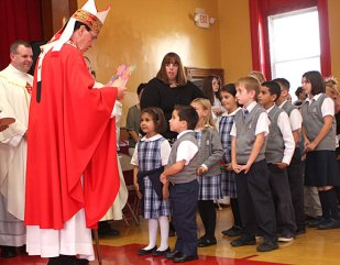 Archbishop Henry Mansell, left, accepts gifts from St. Francis-Hedwig School students Angelina Pires and Jacob Almeida during a ceremony blessing the new Naugatuck school Wednesday morning.