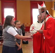 Archbishop Henry Mansell, left, accepts gifts from St. Francis-Hedwig School students Taylor Wade and Nathan Shugdinis during a ceremony blessing the new Naugatuck school Wednesday morning.