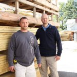 Randy Bushka, left, and Eric Bushka stand in front of a pile of lumber at their 550 High Street store. H.J. Bushka & Sons plans to move to a bigger location in the Naugatuck Industrial Park in the next two years.