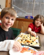 Daniel Anderson, 5, foreground, and Carly Cianflone, 6, background, make nachos Dec. 28 at the Naugatuck Parks and Recreation Department on Rubber Avenue as part of a vacation cooking class for children. The children also made fruit platters and hoagie braids. - LARAINE WESCHLER