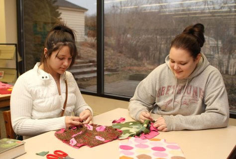 Library volunteers Natalie Garcia, 15, left, and Ashley Shaw, 16, work on a no-sew pillow at the Howard Whittemore Library's teen craft night Feb. 8.