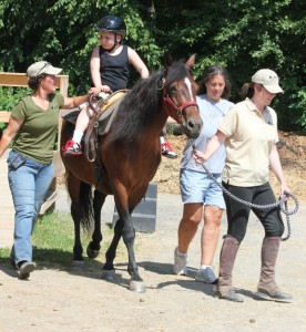 Hidden Acres Therapeutic Riding Center Program Director Jeanna Pellino, left, instructor Rebecca Caruso, right front, and volunteer Nancy Kennedy lead 9-year-old Noah Nadhazi on a ride in 2012 at the center in Naugatuck. The center is initiating a pilot program this month for Naugatuck teens suffering from depression and/or anxiety disorders.  –FILE PHOTO