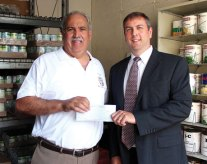 St. Vincent DePaul Mission soup kitchen Food Service Director Paul Scampolino, left, receives a $10,000 check from Craig Porter, vice president and marketing director of Naugatuck Savings Bank recently. The money will benefit the homeless shelter and soup kitchen at the St. Vincent DePaul Mission in Waterbury. -CONTRIBUTED