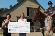 Hidden Acres Therapeutic Riding Center in Naugatuck recently received a $15,000 grant from the Naugatuck Savings Bank Foundation to help pay for a covered riding arena. Pictured, from left, Jayne Kelly, of Naugatuck Savings Bank, Mary Simon, of Hidden Acres, Liz Hocking, of Hidden Acres, and Sean Sears. -CONTRIBUTED