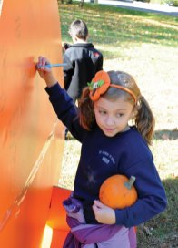Carolina Rychlik signs a giant pumpkin cutout during St. Francis-St. Hedwig School's Fall Festival Oct. 22. The festival included games, snacks, a hay ride, and a pumpkin patch where the students were able to pick a pumpkin. -LUKE MARSHALL