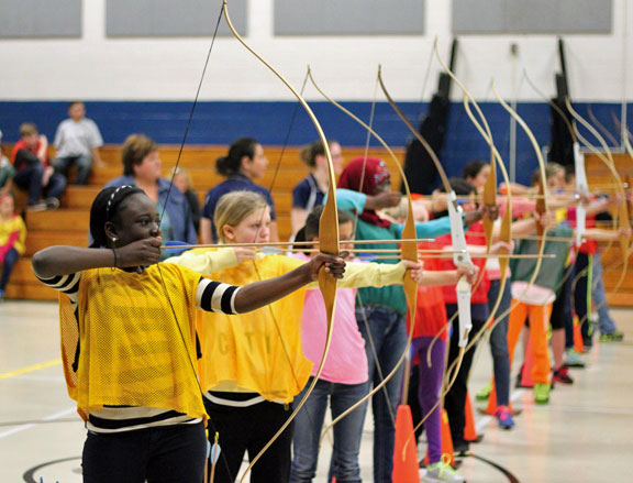 Long River Middle School sixth-graders Cassandra Quayson, front, and Jennifer Galuzy, second from the front, line up their shots Nov. 21 during an archery lesson in gym class. –ELIO GUGLIOTTI