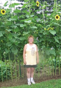 St. Michael's Church parishioner Kimberly Pyka stands in front of sunflowers grown in the church's Harvest Now garden last year. A sunflower was entered in the Bethlehem Fair this past fall and won Best in Show.-CONTRIBUTED