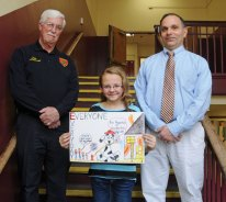 Hillside Intermediate School fifth-grader Hailey Russell, center, holds up her winning fire prevention poster with her teacher Mark Solomito, right, and Acting Deputy Fire Marshall Bill Scanlon, left, at her side in the school in Naugatuck last Friday. Russell's poster won first place in the fifth-grade category at the New Haven County competition. She is the first student from Naugatuck to win the competition in the seven years the borough has been entering the competition. The top four winners from each of the state's eight counties will move on to the state competition and be honored at a luncheon March 27. Russell's poster will also be displayed in the legislative building in Hartford in October, as part of Fire Prevention Month and be featured in a 2014 Fire Prevention calendar. –LUKE MARSHALL