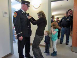 Kathy Flaherty pins a new badge to the uniform of her husband, Stephen 'Greg' Flaherty, who was promoted Wednesday night to captain in the Naugatuck Fire Department. Their grandchildren, 2-year-old Jordyn Alford and 5-year-old Tessa Travali, look on. –RA ARCHIVE