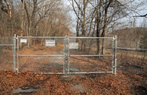 A locked gate with 'No Trespassing' signs blocks public access to the Naugatuck State Forest at the end of Cold Spring Road in Beacon Falls. –FILE PHOTO