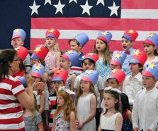 Algonquin School music teacher Fran Grzybowski leads first-graders in a patriotic song May 23 at the school in Prospect during the first grade's annual ceremony to commemorate Memorial Day. –ELIO GUGLIOTTI