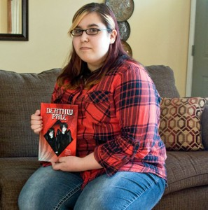 Woodland Regional High School sophomore Kaylee Velez, 16, holds a copy of 'Deathly Pale' by Anthony Paolucci in her home May 1. Velez created the illustrations for the book. Velez and Paolucci will be signing copies of the book from 11 a.m. until 1 p.m. Saturday at the Beacon Falls Public Library. –LUKE MARSHALL