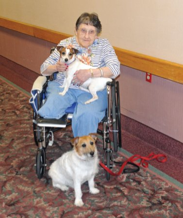 Florence Creatura, a resident of Beacon Brook Health Center in Naugatuck, holds Daisy Mae on her lap while Gunner sits at her feet on May 8. Over a dozen residents were in the center's recreation room, interacting with the dogs. Naugatuck resident Mary Repko, who owns Daisy Mae and Gunner, regularly brings her dogs to the center as therapy dogs. Repko originally brought Gunner to the center about 6 years ago when her parents were residents. She said she saw how people enjoyed them and decided to bring them as therapy dogs. –LUKE MARSHALL