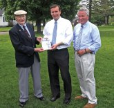 Civil War historian Joseph Gomez, left, presents U.S. Sen. Chris Murphy (D-Conn.) with a copy of his book, 'Not in Vain: A Story of a Soldier' as Mayor Robert Chatfield looks on Wednesday afternoon on the Town Green. –LUKE MARSHALL