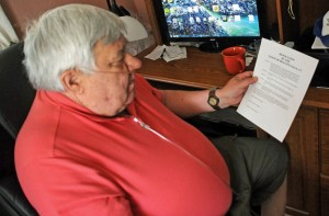 Navy veteran Raymond Melninkaitis, 66, looks over a resolution he wrote for the town to support at his home in Beacon Falls last week. The resolution supports changing what Vietnam War veterans have access to health care benefits regarding health issues from Agent Orange. The Board of Selectman supported the resolution Monday night. –LUKE MARSHALL