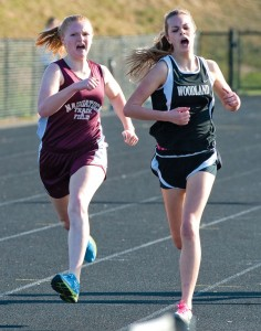 Naugatuck's Madison Beasley, left, overtakes Woodland's Mary Sardinskas in the final 100 meters of the 1,600 meter run for the first varsity win of her career during a meet last month. Beasley, a junior, battled shin issues her first two seasons and has been an unexpected surprise for the Greyhounds this year. –RA ARCHIVE
