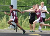 Naugatuck's Enrique DeJesus, left, takes the baton from Brian Rielly during the 4-by-100 relay at the NVL boys track and field championship meet Tuesday in Beacon Falls. Woodland won the meet with 131.5 points as Naugatuck finished fifth with 61.5 points. –LUKE MARSHALL
