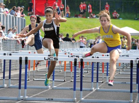 Woodland's Alina Martinez, left, jumps over a hurdle as Seymour's Diana Janus clears a hurdle of her own during the 100 meter hurdles at the NVL girls track and field championships Tuesday in Beacon Falls. The Woodland girls won the meet title, the NVL Brass Division title and the league championship by defeating Watertown, 150-136.5. The Naugatuck girls tied for third with Holy Cross at the meet. –LUKE MARSHALL