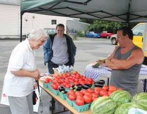 Clem Cardow, left, of Beacon Falls looks over some fresh vegetables from Sunflower Farms in Cheshire as she talks with Martha Berge, an EMT from Beacon Hose Company No. 1, and Joe Sanpieri of Sunflower Farms during opening day of the Beacon Falls Farm  Stand last year. –FILE PHOTO
