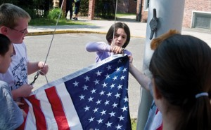 Hop Brook Elementary School fourth-grader Izabelle Tolliver hooks an American flag to raise at the school last Friday morning. The flag was sent to the school by the National Guard's 38th Sustainment Brigade, which is stationed at Camp Arifjan in Kuwait. Tolliver's mother, Sgt. 1st Class Katie Zarzycka, is currently deployed with the unit. –LUKE MARSHALL
