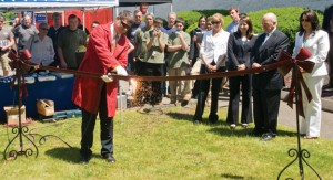 Naugatuck Mayor Robert Mezzo cuts a metal ribbon with a welding torch to welcome Maine Oxy, a supplier of specialty gases, welding supplies and safety equipment, to the borough's industrial park June 20. –LUKE MARSHALL
