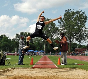 Woodland's Mike Lang sails through the air during the long jump at the State Open track and field meet at Willow Brook Park in New Britain Monday afternoon. Lang placed second at the State Open in the long jump and fifth in the triple jump to qualify for this weekend's New England meet. At the Class M meet last week, Lang finished second in the long jump and third in the triple jump as the Woodland boys took second overall. -RA ARCHIVE
