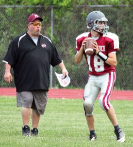 Naugatuck quarterback Jason Bradley scans the field for an open receiver as head coach Craig Bruno watches the offense go to work during the spring scrimmage June 14 at the school. –ELIO GUGLIOTTI