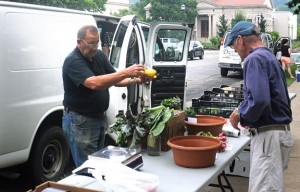 John Marcucio, left, of Marcucio Farms prepares to ring up Paul Becker of Naugatuck for yellow squash July 10 on the Town Green during opening day of the Naugatuck Farmers' Market. –LUKE MARSHALL