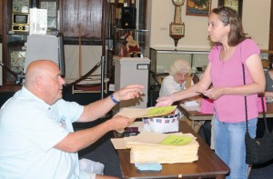Ballot Clerk John Kochis, left, hands Kathleen Cavoto a ballot during Naugatuck's referendum on the 2013-14 municipal and school budgets July 9. Both budgets were adopted after the referendum failed to get the required 15 percent voter turnout. –FILE PHOTO