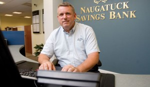 Robert Voets, a former West Haven police officer, works on a computer at Naugatuck Savings Bank in Naugatuck where he helps customers with computer fraud and security issues in Naugatuck. –RA ARCHIVE