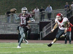 Naugatuck's Jason Bradley (13) throws a pass as Wolcott's Philip Lebel (84) rushes off the edge Sept. 20 in Naugatuck. The Greyhounds won the game, 42-36, in overtime. –ELIO GUGLIOTTI
