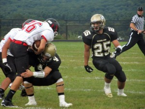 Woodland's Sean McAllen (4) makes a tackle in front of Coby Vaccarelli (25) Sept. 13 against Branford in Beacon Falls. –KYLE BRENNAN