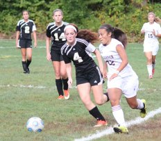 Woodland's Audra Blewitt (4) defends Naugatuck's Stefanie Flores (22) Sept. 13. Blewitt, a senior, switched to the center-midfield position this season and has stepped forward as the Hawks' leader on the pitch. –FILE PHOTO